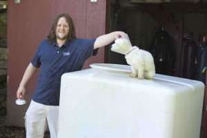 Jake Bassett cleaning tanks with some canine assistance. ABE LOOMIS